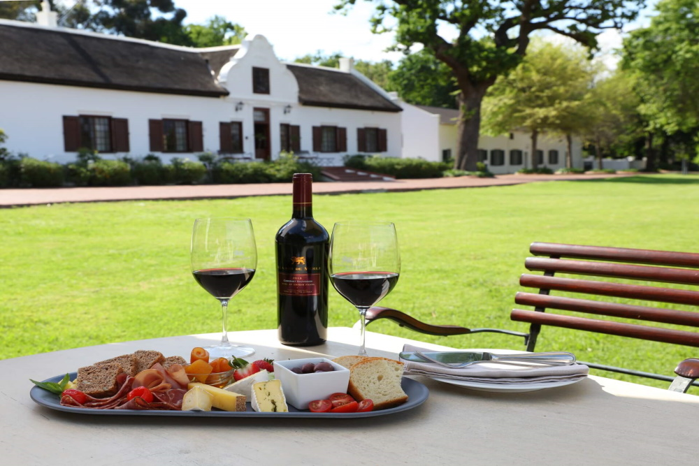 Table with cheese platter and two glasses of Plaisir de Merle Cabernet Sauvignon red wine