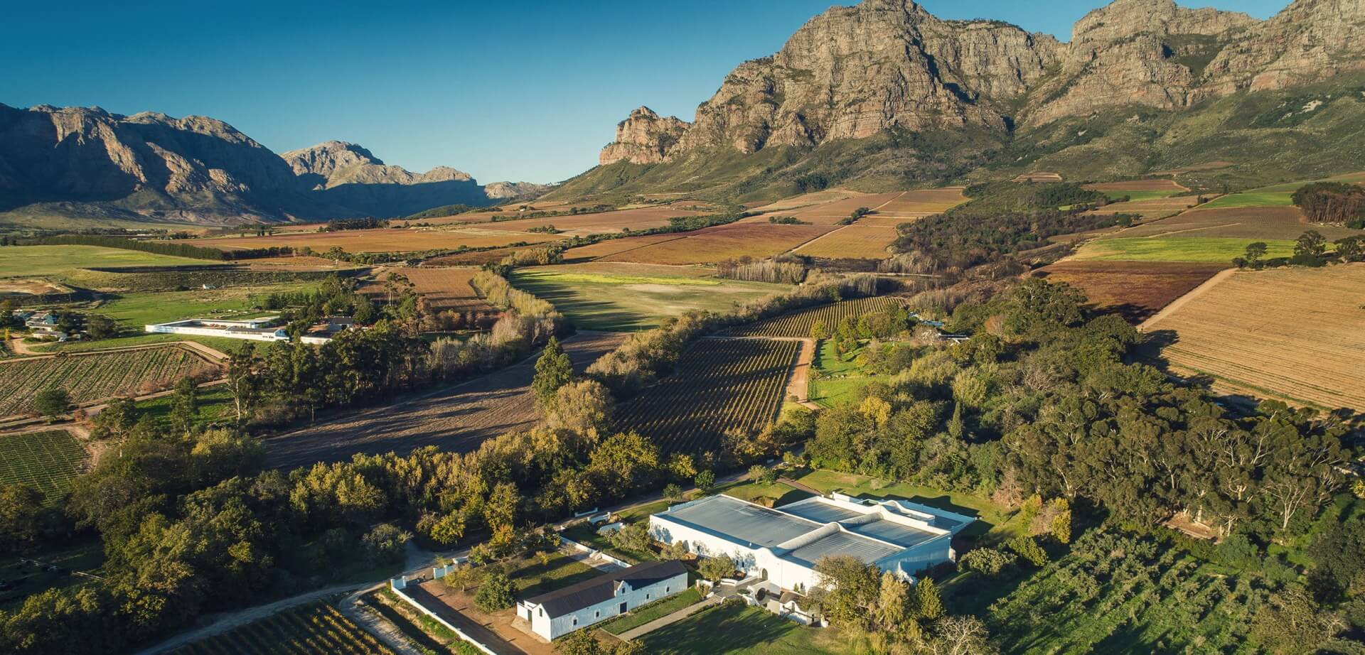 Aerial view of the Plaisir de Merle wine estate in Franschhoek, with mountains and vineyards in the background.